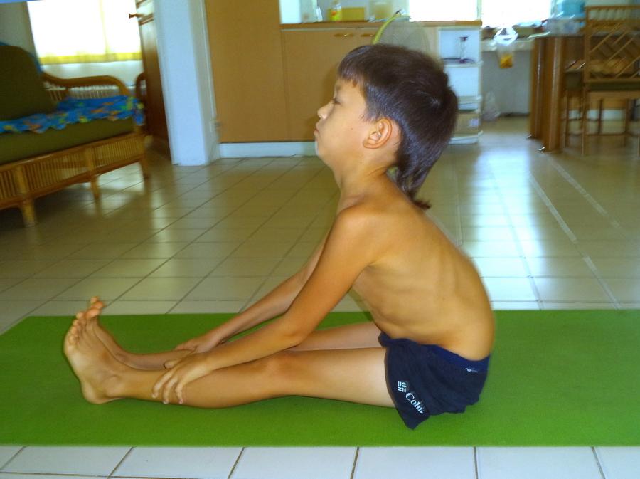 Мальчик в пашчиматанасане в начале курса йоги